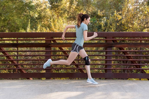 Image of a female running over a bridge wearing a knee brace