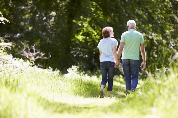 Elderly couple walking through a meadow with trees in the background | OA Knee Pain