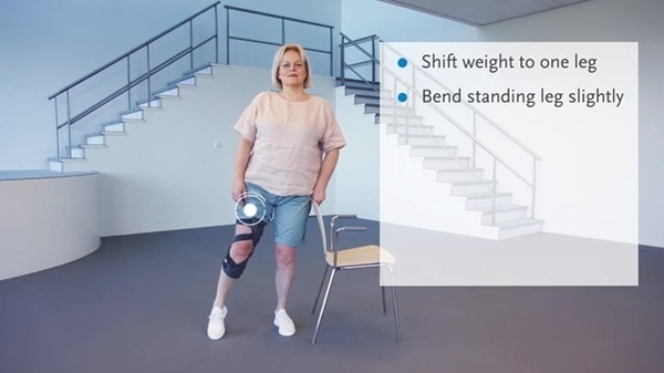 Image of a female performing knee osteoarthritis exercises using a chair whilst wearing a knee brace