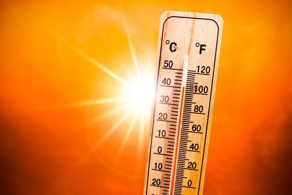 Image of a thermometer in front of a setting sun to signify a high temperature
